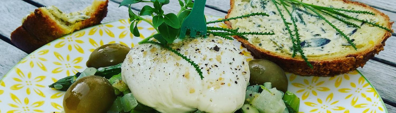 vegane Mozzarella auf Salatbett mit Oliven und knusprigem Brot